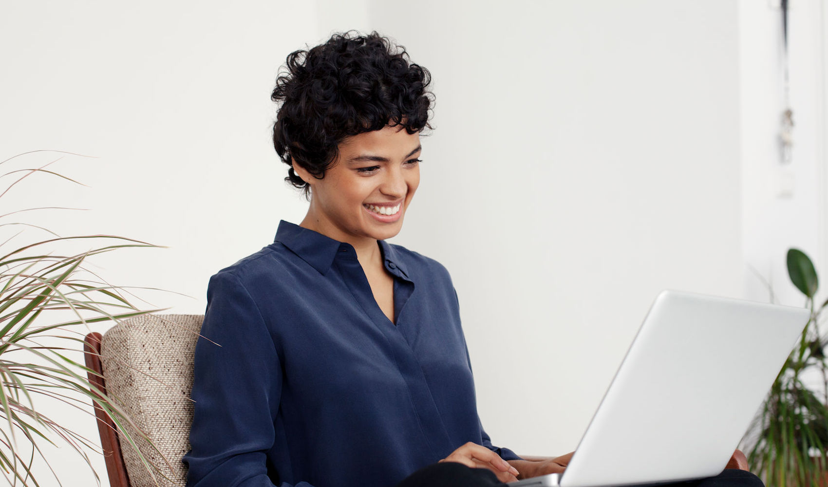 Portrait Of A Woman Using A Laptop Computer In Her Home.
