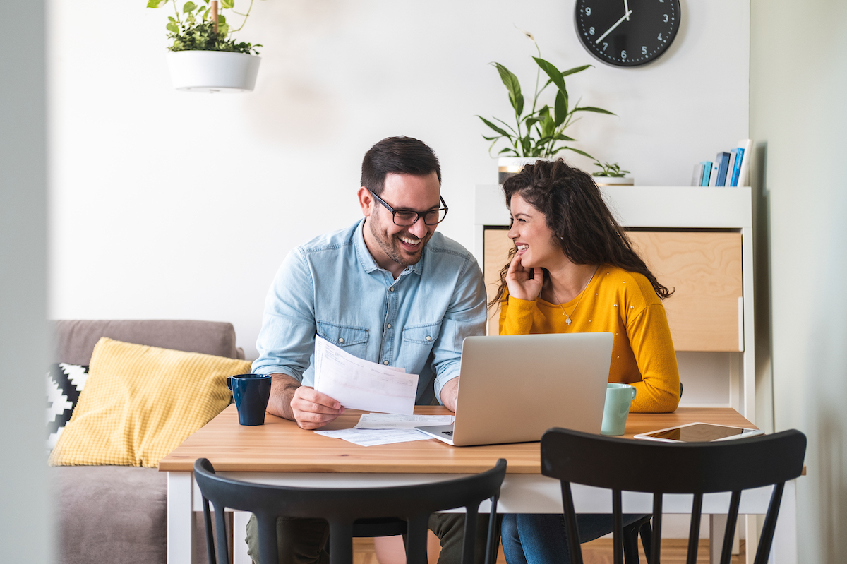 smiling couple managing finances, reviewing their bank accounts using laptop computer and calculator at modern kitchen stock photo